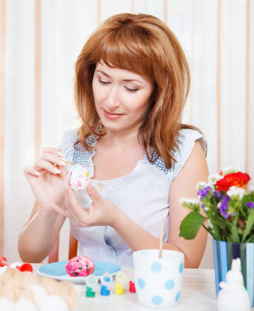 Happy young woman painting Easter eggs Stock Photo - 17991700