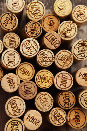 wine tasting: Dated wine bottle corks on the wooden background. Close up
