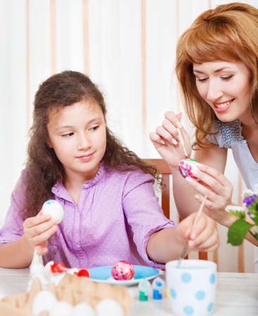 Happy mother and her little daughter painting on Easter eggs photo