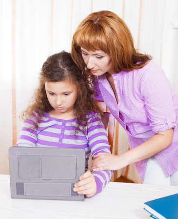 Young woman with girl using tablet computer indoors photo