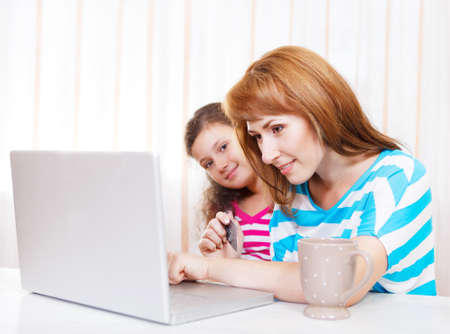 Young woman with daughter using laptop computer at home photo