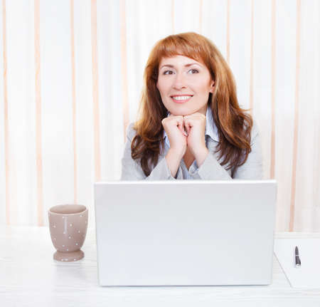 Portrait of happy young business woman on her workplace photo