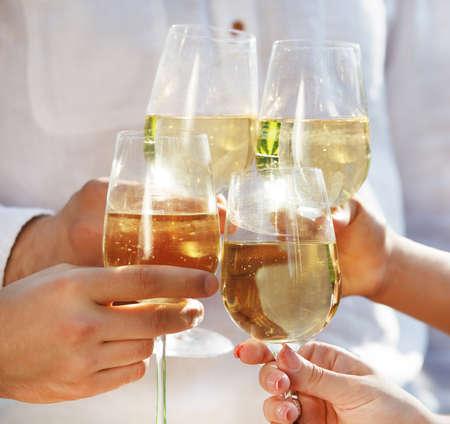 white wine glass: Celebration. People holding glasses of white wine making a toast