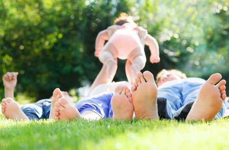 family picnic: Joven familia feliz acostado en la hierba verde al aire libre en el parque de verano