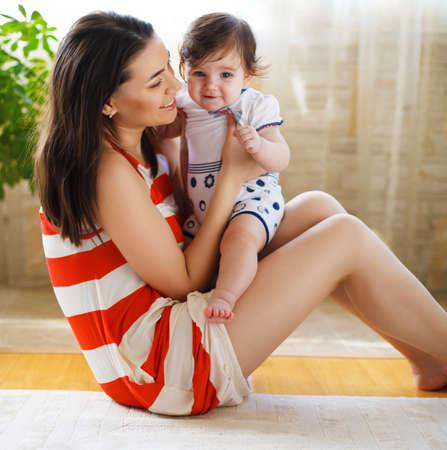 madre y bebe: Feliz sonriente madre con ocho meses de edad ni�a interior
