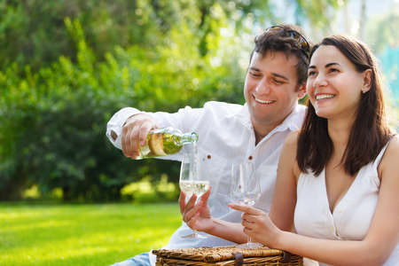 Young happy couple enjoying a glasses of white wine in the garden