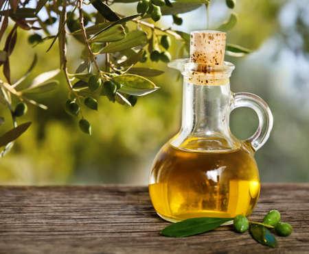 Aceite de oliva y rama de olivo en la mesa de madera sobre el fondo de la naturaleza Foto de archivo
