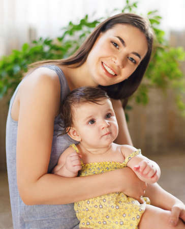 infants: Happy smiling mother with eight month old baby girl indoor Stock Photo