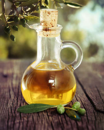 maturation: Olive oil and olive branch on the wooden table over nature background