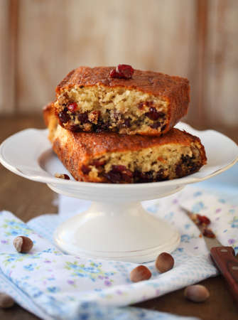 Homemade cranberry cake with hazelnuts (filbert) over wooden background photo