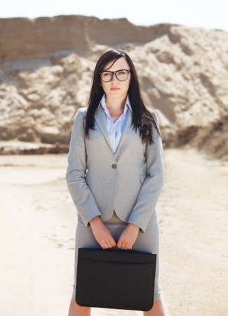 gray suit: Portrait of the brunette business woman in a desert