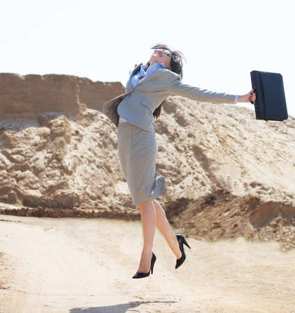 Happy businesswoman jumping in the air in a desert photo