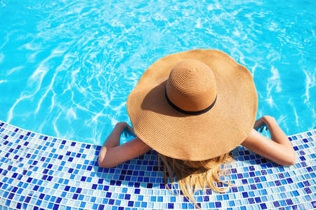 Pretty woman in a hat enjoying a swimming pool Stock Photo - 18465053