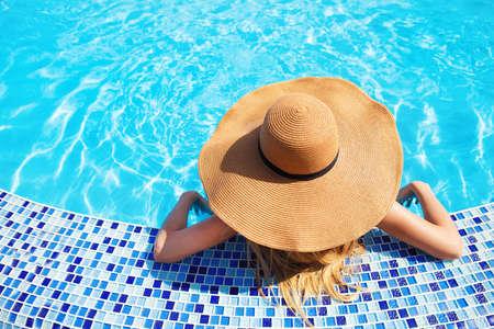 Pretty woman in a hat enjoying a swimming pool Stock Photo - 18465053