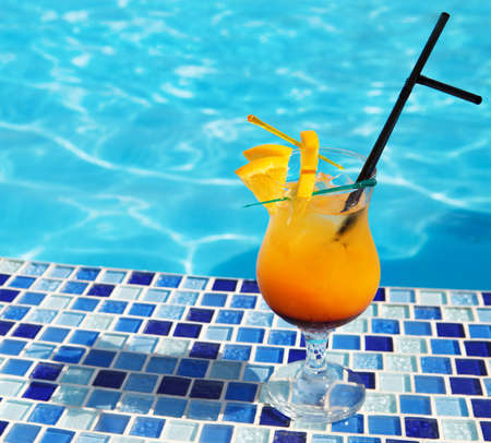 cocktail drinks: Bright orange cocktail stands on edge of pool  Stock Photo