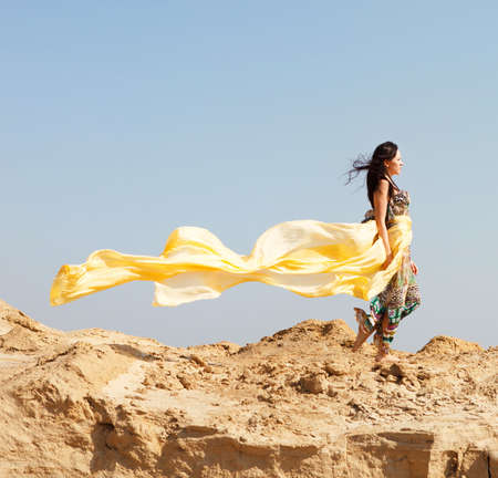 Beautiful young woman walking in a desert photo