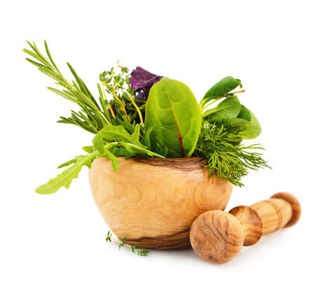 Mortar with fresh herbs isolated on white background