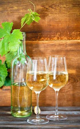 white wine bottle: Naturaleza muerta con vasos de vino blanco botella, y las hojas Foto de archivo