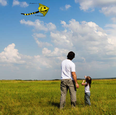 flying kite: Little girl and her father with flying a kite on the summer field Stock Photo