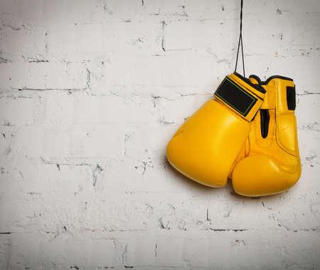 guantes de boxeo: Un par de guantes de boxeo color amarillo que cuelga en una pared de ladrillo