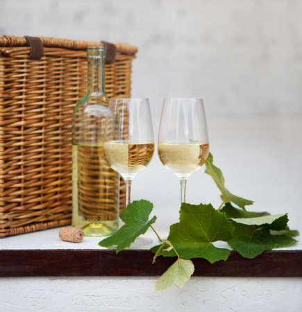maturing: Still life with glasses of white wine, bottle, basket and leaves of grape