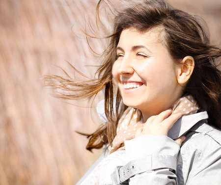 Portrait of a smiling brunette in windy day. Close up photo