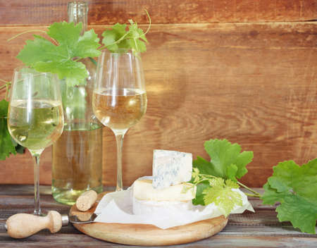 intoxicant: Still life with glasses of white wine, bottle and cheese Stock Photo