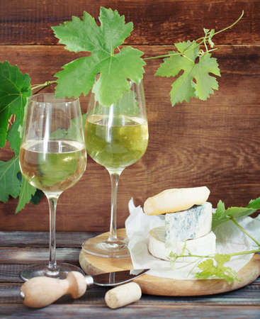 Still life with glasses of white wine, bottle and cheese Stock Photo