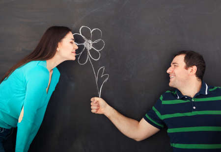 two and a half: Young happy couple with daisy flower. Chalk drawing on dark background