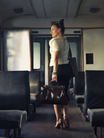 station wagon: Woman with a suitcase walking in wagon in the retro train Stock Photo