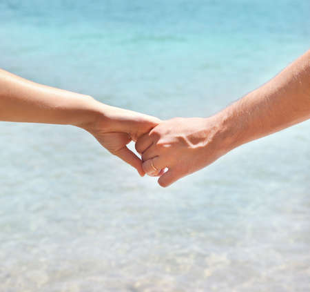 holding close: Young couple in love holding hands. Summer sea background. Close up Stock Photo