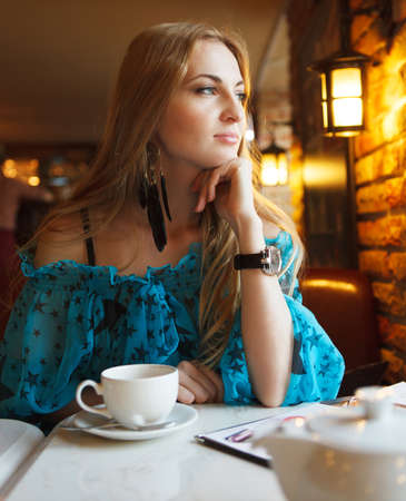Smiling woman drinking coffee smiling in cafe photo