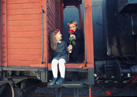 little boy gives red rose to the little girl in the retro train Stock Photo - 20082245