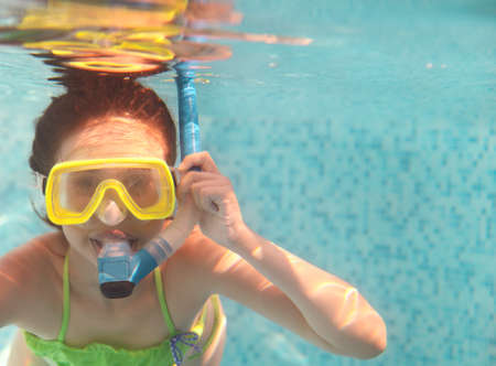 The little girl swimming underwater and smiling. Shot was taken with waterproof box photo
