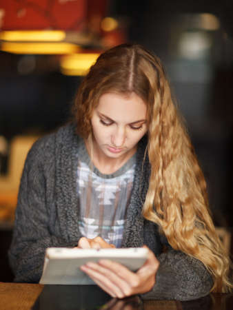 Young woman with touch screen tablet computer in cafe photo