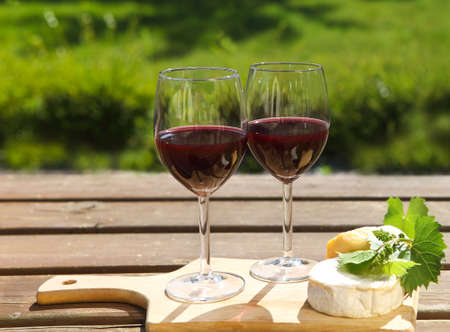 sorts: Various sorts of cheese, grape leaves and two glasses of the natural homemade red wine