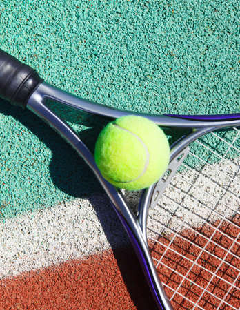 Close up of tennis racquet and ball on the clay tennis court photo