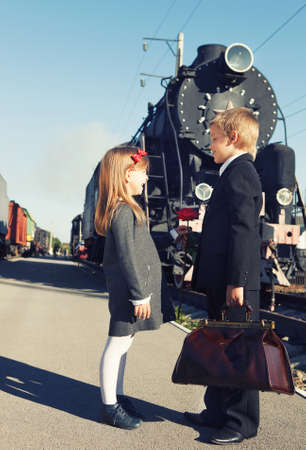 give way: little boy gives red rose to the little girl near the retro train Stock Photo