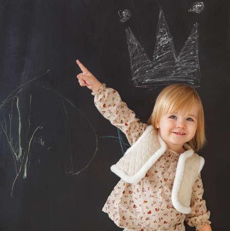 niños dibujando: Niña linda que se divierte. Dibujo de tiza sobre fondo oscuro