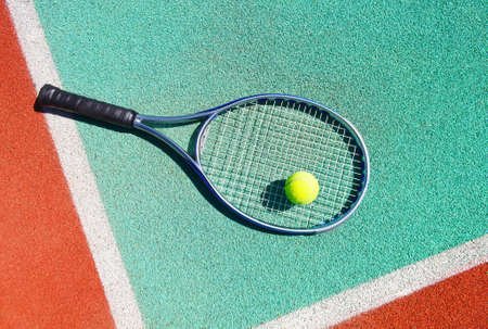 avocation: Close up of tennis racquet and ball on the clay tennis court