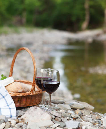 Red wine, cheese and bread served at a picnic. Mountain river background photo