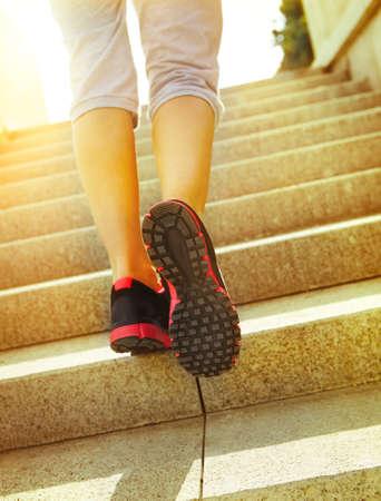 Runner feet running on road closeup on shoes. Woman fitness sunrise jog workout welness concept