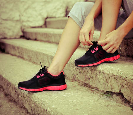Athlete girl trying running shoes getting ready for jogging photo