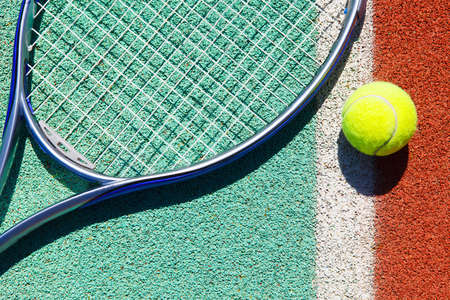 raqueta de tenis: Cerca de la raqueta de tenis y la pelota en la cancha de tenis de arcilla Foto de archivo