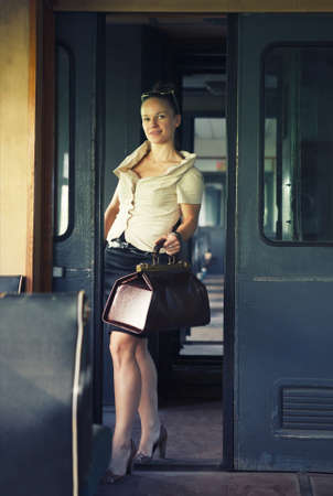 Woman with a suitcase walking in wagon in the retro train photo