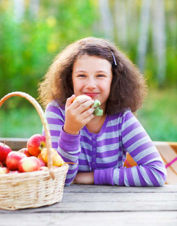 Smiling little girl with basket of red apples in autumn park photo