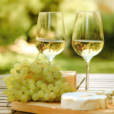vinos y quesos: Varios tipos de queso, uvas y dos vasos de vino blanco