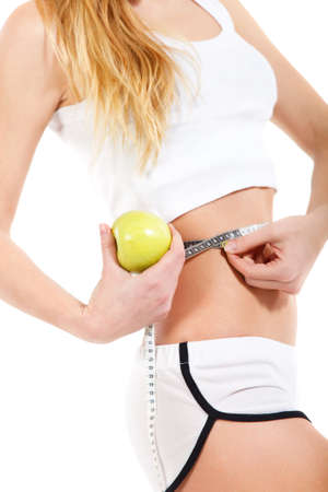 girth: Woman holding apple and measuring her waist on white background Stock Photo