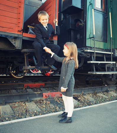 little boy and little girl near the retro train photo