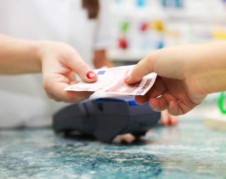 transaction: Close up on paying for medicine using cash at pharmacy Stock Photo